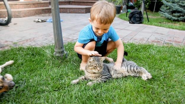 Portret ślicznego 3-letniego chłopca siedzącego na trawie i pieszczącego szarego kota