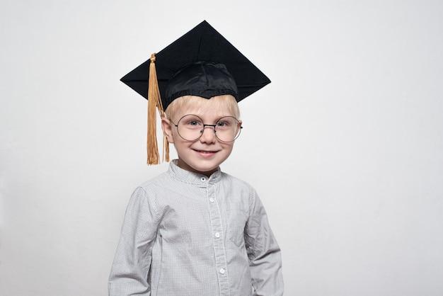 Portret ślicznego blond chłopiec w dużych szkłach i akademickim kapeluszu.