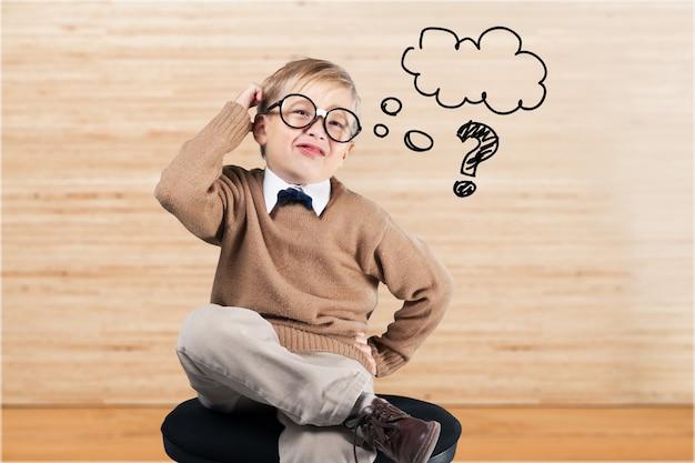 Portret ślicznego chłopca w okularach myślącego nad tłem