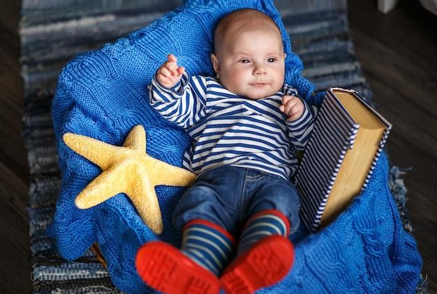 Portret ślicznego chłopca w pasiastej kamizelce i butach we wnętrzu w morskim stylu
