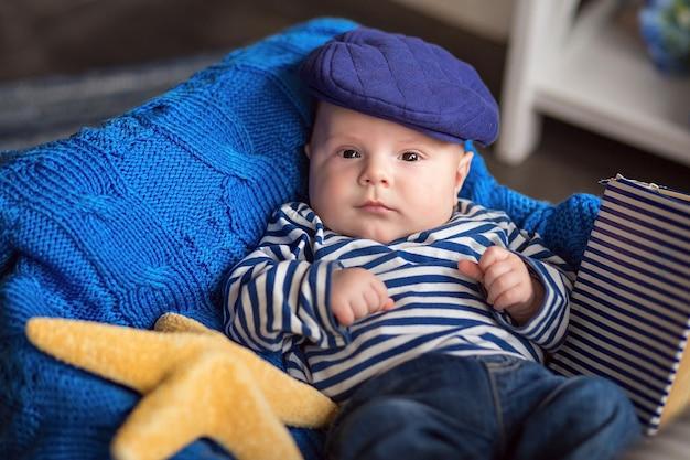 Portret ślicznego chłopca w pasiastej kamizelce i czapce we wnętrzu w morskim stylu