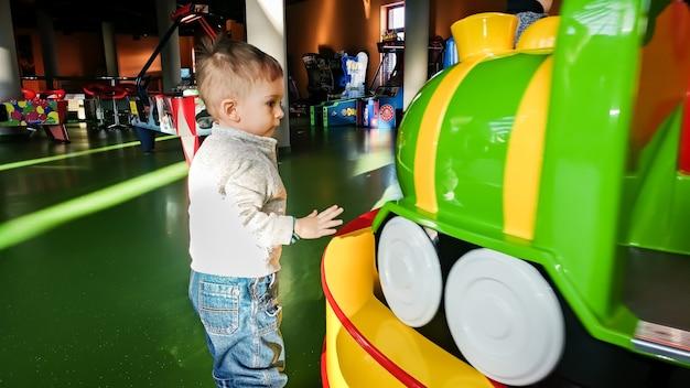 Portret ślicznego małego chłopca patrzącego na kolorową karuzelę z pociągiem w parku rozrywki