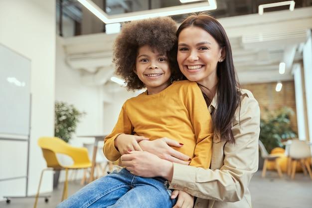 Portret ślicznego małego chłopca z afro włosami uśmiecha się, pozując do kamery razem z pięknymi