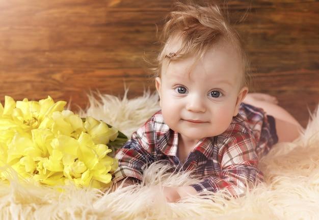 Portret ślicznego małego dziecka leżał na brzuchu w pobliżu żółtych tulipanów, wielkie oczy.