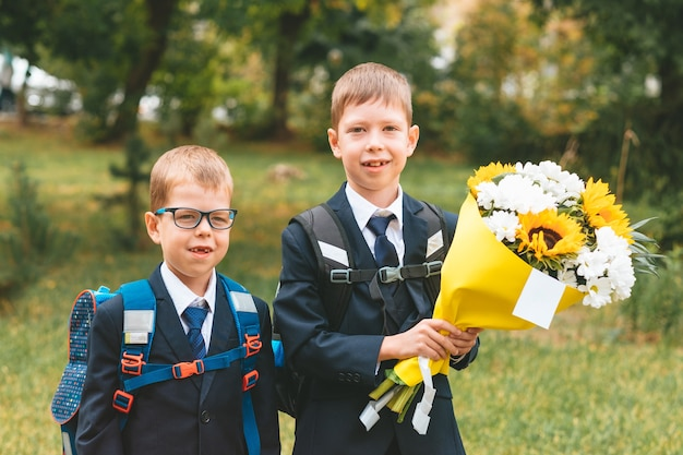 Portret ślicznego małego siedmioletniego pierwszego równiarki trzymającego bukiet kwiatów z bratem
