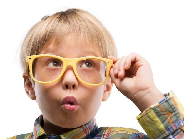 Portret ślicznego młodego chłopca w okularach myślącego nad białym tłem