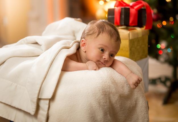 Portret ślicznego noworodka leżącego na brzuchu obok prezentów świątecznych