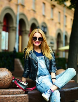 Portret ślicznego śmiesznego blond nowożytnego seksownego miastowego młodego eleganckiego kobiety dziewczyny modela w jaskrawym nowożytnym płótnie outdoors siedzi w parku w cajgach na ławce w szkłach