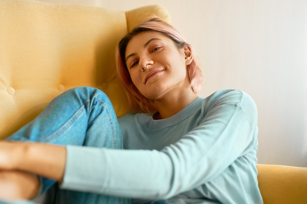 Portret ślicznej 20-letniej dziewczyny z kolczykiem w nosie i różowymi włosami, leniuchującej w fotelu w swobodnym ubraniu o zrelaksowanym beztroskim wyrazie twarzy.