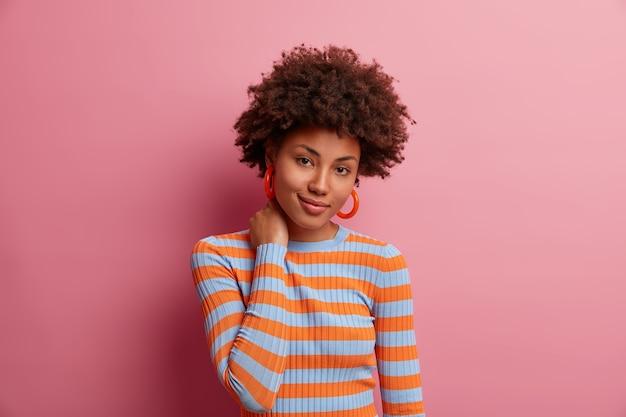 Portret ślicznej ciemnoskórej tysiącletniej dziewczyny dotyka szyi i wygląda z uroczym wyrazem, widzi coś, czego chce, ma kręcone, krzaczaste włosy, ubrana niedbale, odizolowana na różowej ścianie