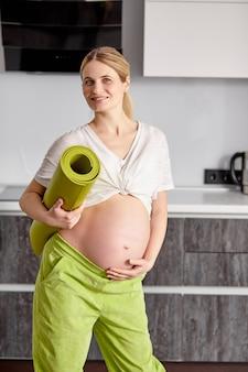 Portret ślicznej ciężarnej kobiety głaszczącej dotykającą brzuch momtobe, oczekującej stojaka na dziecko z matą fitness po jodze