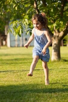 Portret ślicznej dziewczynki, która bawi się kolorową piłką na wiejskim podwórku