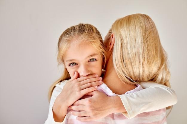 Portret ślicznej dziewczynki przytulającej matkę, smażony rodzic uspokaja swoją kochającą córkę w domu