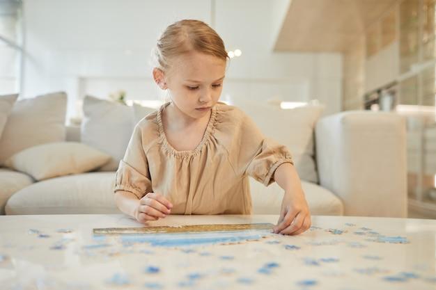 Portret ślicznej dziewczynki rozwiązującej puzzle, ciesząc się czasem w domu