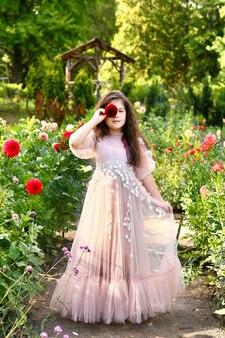 Portret ślicznej dziewczynki z długimi włosami, ubrana w długą lekką sukienkę na zewnątrz w polu dalii