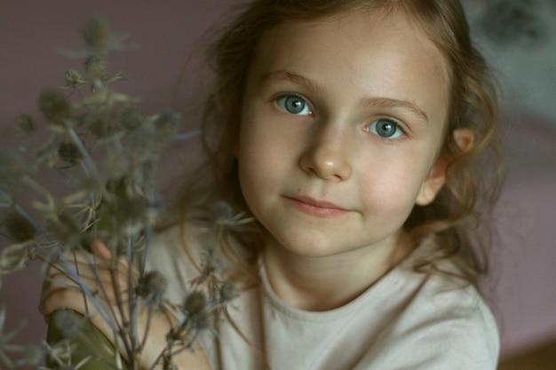 Portret ślicznej dziewczynki z kręconymi włosami i dużymi niebieskimi oczami siedzącej na zielonym krześle w pokoju w lekkiej sukience z bukietem suszonych kwiatów ostu