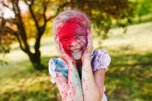 Portret ślicznej dziewczyny malowanej w barwach festiwalu holi.