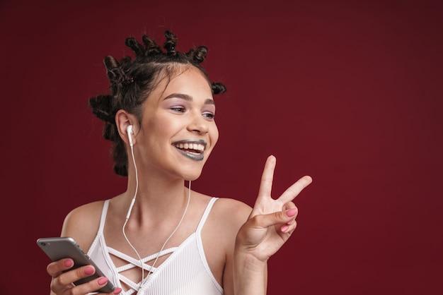 Portret ślicznej dziewczyny punk z dziwaczną fryzurą i ciemną szminką pokazującą palce pokoju podczas korzystania ze smartfona ze słuchawkami na białym tle nad czerwoną ścianą
