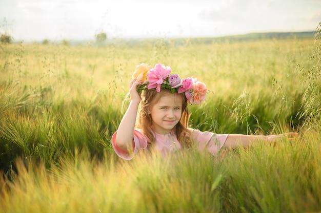 Portret ślicznej dziewczyny w różowej sukience. dziewczyna pozuje w zielonym polu pszenicy.