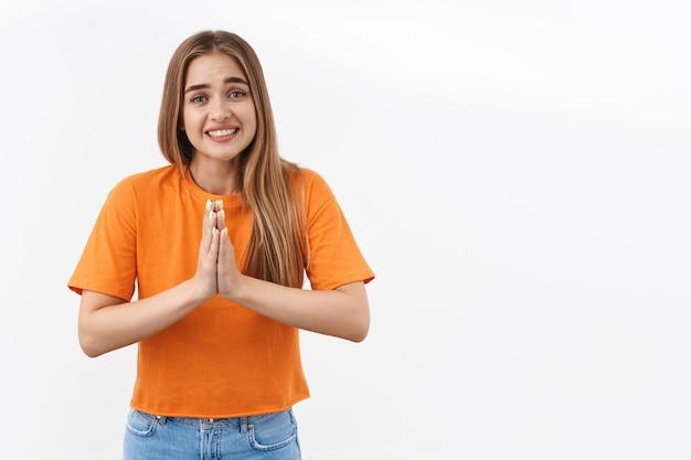 Portret ślicznej, głupiej dziewczyny potrzebuje pomocy jak najszybciej, zaciska zęby, uśmiechając się błagalnie, trzyma ręce razem w modlitwie, mów proszę, błagając o łaskę, pożyczając pieniądze od przyjaciela, prosząc o coś