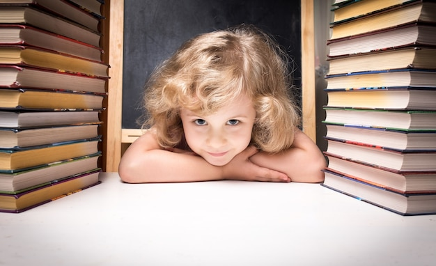 Portret ślicznej inteligentnej dziewczyny uśmiecha się siedząc ze stosem książek przy stole