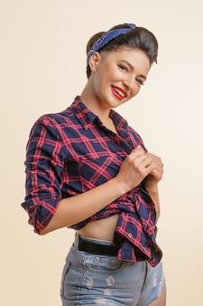 Portret ślicznej kobiety z makijażem w jeansowych szortach i koszuli pozującej w uroczym uśmiechu