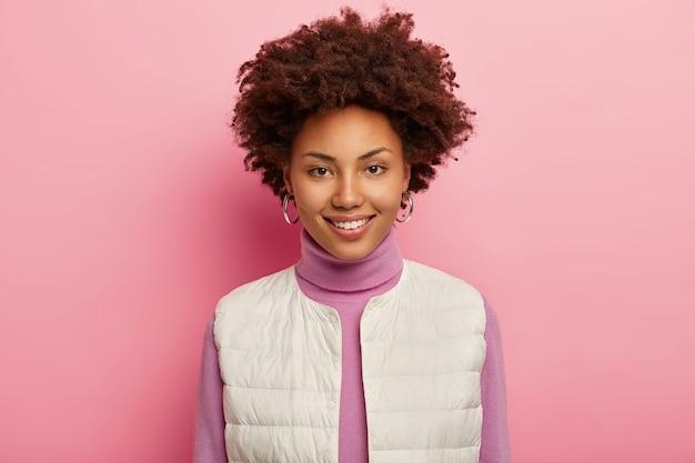 Portret ślicznej, kręconej kobiety ma naturalne piękno, sympatycznie się uśmiecha, nosi kolczyki, białą kamizelkę, wyraża radość, pozuje na różowym tle.