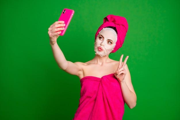 Portret ślicznej ładnej damy noszącej turban za pomocą maski na twarz biorącej selfie pokazujące znak v wargi na białym tle na jasnozielonym tle