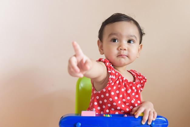 Portret ślicznej małej azjatyckiej dziewczyny ubranej na czerwono, siedzącej z palcem skierowanym do przodu, odizolowanej na tle koncepcji wyrażenia dziecka