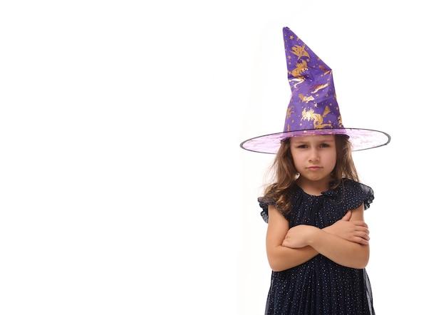 Portret ślicznej małej czarownicy zły zdenerwowany dziewczyna w kapeluszu czarodzieja i ubrana w stylową sukienkę karnawałową, patrząc na kamerę pozującą ze skrzyżowanymi rękami na białym tle, kopia przestrzeń, halloween