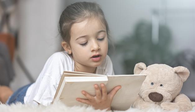 Portret ślicznej małej dziewczynki czytającej książkę w domu, leżącej na podłodze ze swoją ulubioną zabawką.