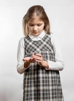 Portret ślicznej małej dziewczynki liczącej palce na białym tle