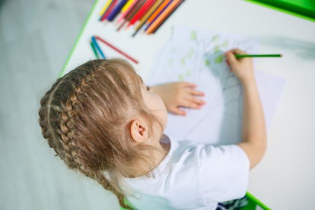 Portret ślicznej małej dziewczynki patrzącej w kamerę i uśmiechającej się podczas rysowania zdjęć lub odrabiania lekcji, siedząca przy stole we wnętrzu domu, kopia przestrzeń