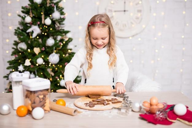 Portret ślicznej małej dziewczynki pieczenia ciasteczek świątecznych w kuchni z choinką