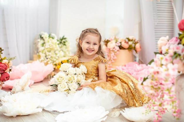 Portret ślicznej małej dziewczynki w pięknej sukni z falistym, z bukietem róż.