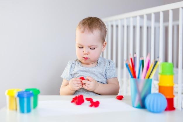 Portret ślicznej małej dziewczynki w wieku przedszkolnym bawiącej się plasteliną w swoim pokoju