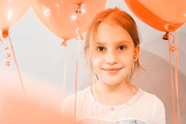 Portret ślicznej małej szczęśliwej szczerej uśmiechniętej kaukaskiej ośmioletniej dziewczynki z czerwonymi balonami na tle szarej ściany podczas obchodów jej urodzin w domu