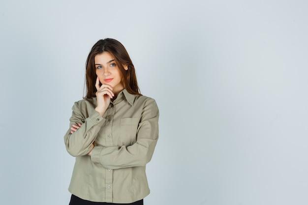 Portret ślicznej młodej kobiety trzymającej rękę na brodzie w koszuli i wyglądającej rozsądnie z przodu