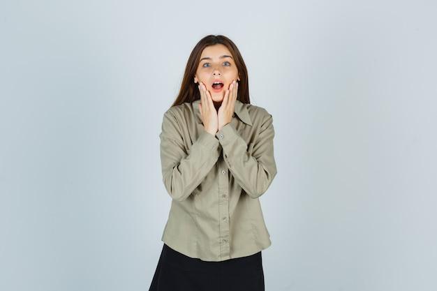 Portret ślicznej młodej kobiety trzymającej się za ręce na policzkach w koszuli, spódnicy i patrząc zdziwionym widokiem z przodu