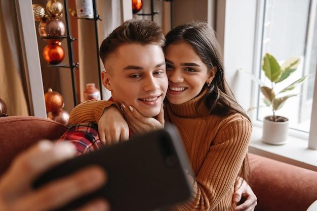 Portret ślicznej młodej pary kochającej siedział w kawiarni w pomieszczeniu weź selfie przez telefon komórkowy.