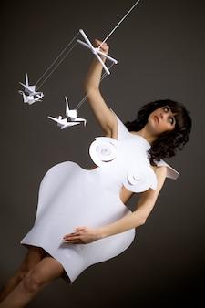 Portret ślicznej młodej smutnej dziewczyny w sukni origami z ruchomymi ramionami jak marionetka dotykająca latających papierowych ptaków na czarnym tle