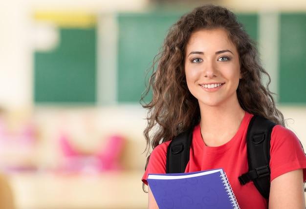 Portret ślicznej młodej studentki trzymającej kolorowy notatnik, odizolowane na tle