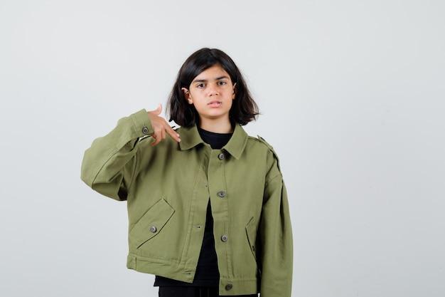 Portret ślicznej nastolatki wskazującej na siebie palcem pistoletem w zielonej kurtce i patrzącej na zdenerwowany widok z przodu