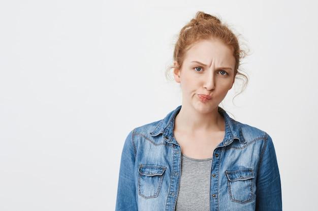 Portret ślicznej nieszczęśliwej rudowłosej dziewczyny rasy kaukaskiej, marszczącej brwi i mrużących oczy, gdy jest zaniepokojona lub waha się