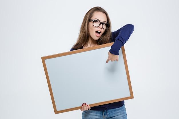 Portret ślicznej pięknej kobiety wskazującej palcem na pustej desce na białym tle
