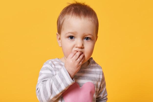 Portret ślicznej rozmyślającej dziewczyny z krótkimi jasnymi włosami trzymającymi palce w ustach. poważne dziecko stoi przed kamerą i patrzy prosto