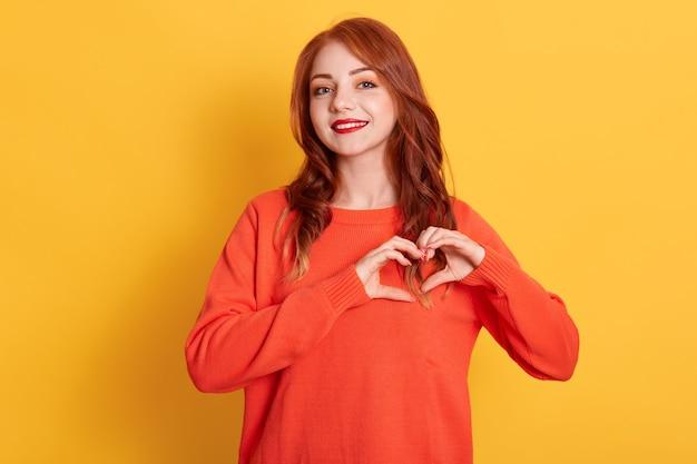 Portret ślicznej rudowłosej modelki robi gest serca, demonstruje znak miłości, ma szczęśliwy wyraz twarzy, ubrana w pomarańczowy sweter, pozuje na żółtym tle.