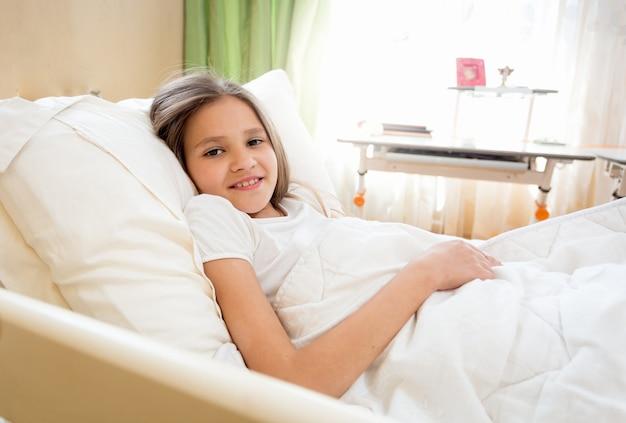 Portret ślicznej uśmiechniętej dziewczyny leżącej w łóżku w słoneczny poranek