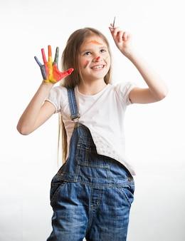 Portret ślicznej uśmiechniętej dziewczyny z pomalowaną twarzą i rękami rysującymi w powietrzu