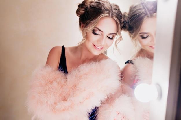 Portret ślicznej uśmiechniętej dziewczyny z stylowym profesjonalnym makijażem czekającej na modową sesję zdjęciową. urocza młoda kobieta pozuje w szatni w futrzanej kurtce z zamkniętymi oczami